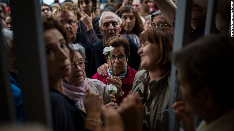 People wait at the doors of a school in Barcelona to start voting during the Catalan independence referendum.