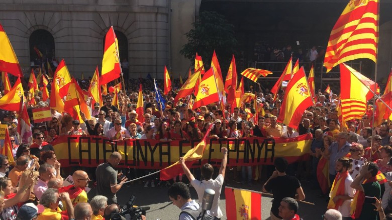 """Protesters hold a banner that reads """"Catalonia is Spain"""" at the pro-unity rally in Barcelona on Sunday."""