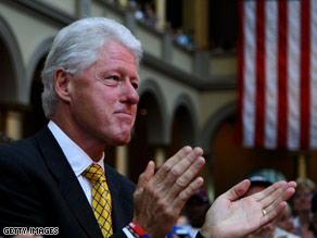 Former President Clinton watches his wife announce that she is suspending her campaign Saturday.