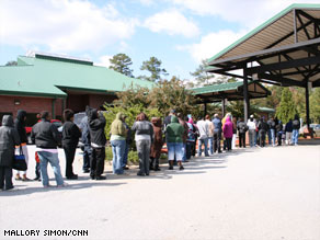Hundreds of people stand in line outside the Frank Bailey Senior Center Tuesday in Riverdale, Georgia.