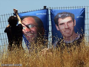 "An Israeli hangs posters of the soldiers Eldad Regev, right, and Ehud ""Udi"" Goldwasser last month in Jerusalem."