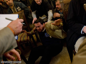 An Iraqi man is grabbed after throwing his shoes at Bush during a news briefing Sunday in Baghdad.