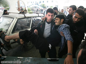 A wounded man is lifted onto a stretcher after arriving at Shifa Hospital in Gaza City on Sunday.