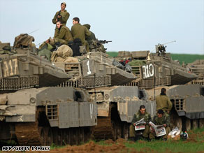 A column of Israeli armored vehicles is deployed in a farmer's field Tuesday near the Gaza border.