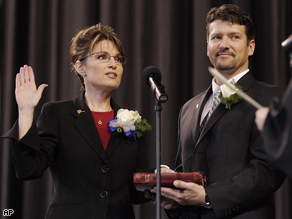 Todd Palin holds the Bible for his wife, Sarah Palin, as she is sworn in as Alaska's governor in Fairbanks, Alaska, Dec. 4, 2006.