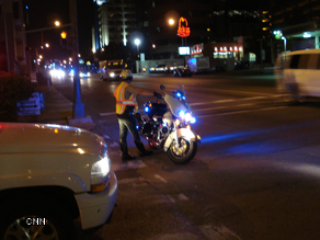 A policeman directs traffic while awaiting a motorcade in Nashville.