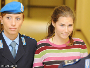 Amanda Knox, suspect in Kercher's death, is escorted out when leaving a court hearing in Perugia, Italy yesterday.