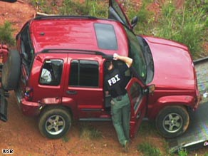 Authorities examine a Jeep belonging to professor George Zinkhan on May 1 in Clarke County, Georgia.