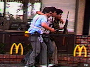 Police help a wounded customer out of a California McDonald's where a man killed 21 people in 1984.