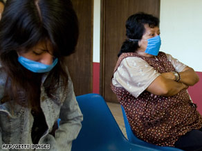 Women wearing masks wait at a health clinic Saturday in Mexico City.