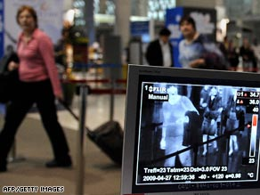 Quarantine officers monitor arrivals with a thermographic device at Bangkok's main international airport.