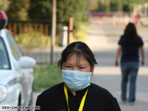 A worker walks outside a Chinese hotel where officials have quarantined visitors as a precaution against swine flu.