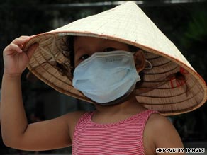 A young girl wears a mask at a hospital in Hanoi. Vietnam reported its first death from swine flu this week.