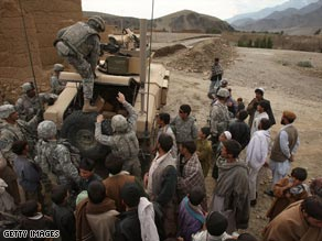 Members of the U.S Army 1-6 Field Artillery division distribute aid to villagers in Tupak, Afghanistan Saturday.