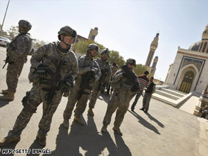 U.S. soldiers stand guard outside a mosque during a prisoner release Sunday in Baghdad, Iraq.
