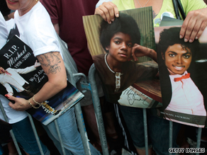 Images of Michael Jackson like these held by fans at the Apollo Theater may prove profitable to his estate.