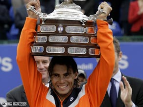 Rafael Nadal lifts the massive Barcelona Open trophy for the fifth year in a row after his win over David Ferrer.