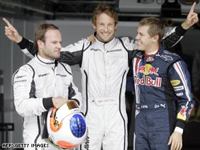 Bright as a Button: Jenson, center, celebrates pole in Spain flanked by Barrichello, left, and Red Bull's Vettel.