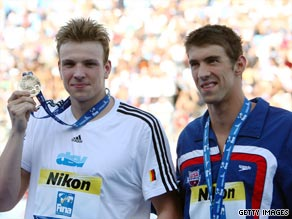 Michael Phelps looks on as Paul Bierdermann (left) shows off his world 200m freestyle gold medal.