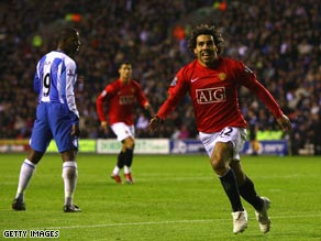 Carlos Tevez celebrates his equalizing goal as Manchester United edged closer to retaining their title.