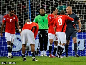 Egypt players protest to referee Howard Webb after his penalty award.