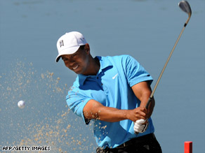 Woods shoots from the bunker on the 3rd hole on Wednesday.