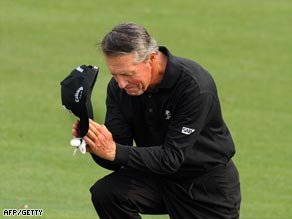 Player doffs his cap to the crowd gathered around the 18th at Augusta.