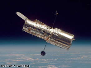 The Hubble Space Telescope hangs above Earth in a 1997 photo taken from the shuttle Discovery.