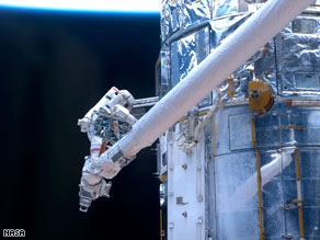 An astronaut works on the Hubble Space Telescope during a spacewalk Monday.
