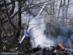 Smoke rises from the tail section of the Continental turboprop at the crash site near Buffalo on Friday.