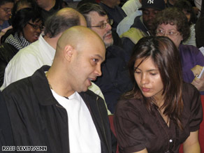 Victor Guavares discusses his plans with his wife, Yajaira, to bid on a foreclosure at an auction Sunday in New York.