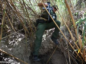 A Border Patrol agent moves through dense cane on the banks of the Rio Grande near Laredo, Texas, last year.