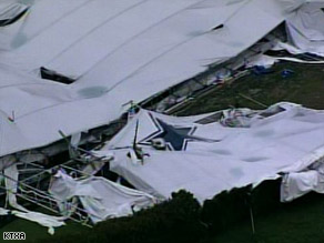 An aerial view of the scene shows the Dallas Cowboys logo amid the ruins of the indoor practice facility.