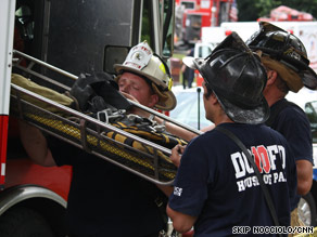 Firefighters pull a stretcher off a firetruck at the scene of Monday's D.C. Metro crash.