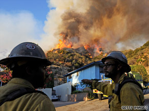 Firefighters stand by Monday as a wall of flames from a backfire light up a hillside in La Crescenta, California.