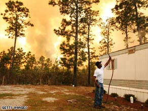 Scott Vereen sprays water on his family's home Thursday near Conway, South Carolina.