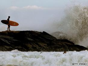 A surfer waits to ride Hurricane Bill-generated waves Saturday at New York's Rockaway Beach.