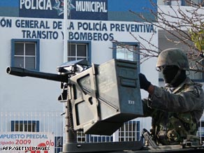 A Mexican soldier guards the entrance at a Cancún police station where the military is investigating a murder.