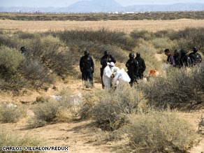 Forensic investigators and federal police dig bodies out of mass graves in the desert near Juarez.