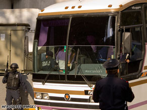 Federal policemen in Mexico City escort a bus with arrested officials from Michoacan state Tuesday.