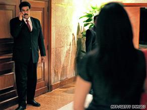Venezuelan Foreign Minister Nicolas Maduro talks on the phone with President Hugo Chavez in Caracas Monday.
