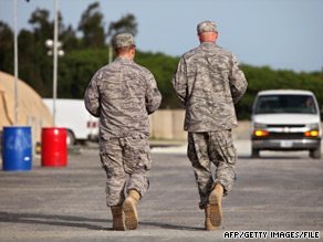 U.S. military personnel walk a road at the U.S. naval base at Guantanamo Bay, Cuba, in July.