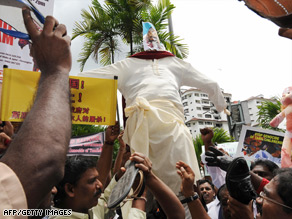 Ethnic Tamils beat an effigy of Sri Lanka's Prime Minister with shoes in front of the U.N. office in Kuala Lumpur.