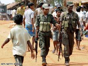 Sri Lankan soldiers patrol a shelter for war-displaced Tamils in Vavuniya in late February.