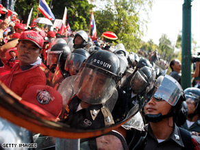 Supporters of former PM Thaksin Shinawatra confront riot policemen outside Government House.