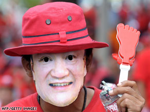 A supporter of former premier Thaksin Shinawatra wearing his mask at a protest in Bangkok on Thursday.