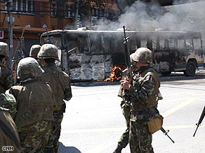 Thai troops pass a smoldering bus during unrest this week in central Bangkok.