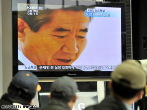 South Korean travelers watch on TV former President Roh Moo-Hyun at a railway station in Seoul on Thursday.