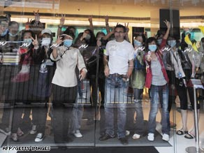 Quarantined guests and hotel employees wave through the glass of the main entrance of Hong Kong's Metro Park Hotel.