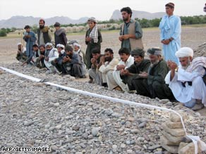 Villagers pray at a mass grave this week after an airstrike in  Afghanistan's Farah Province.